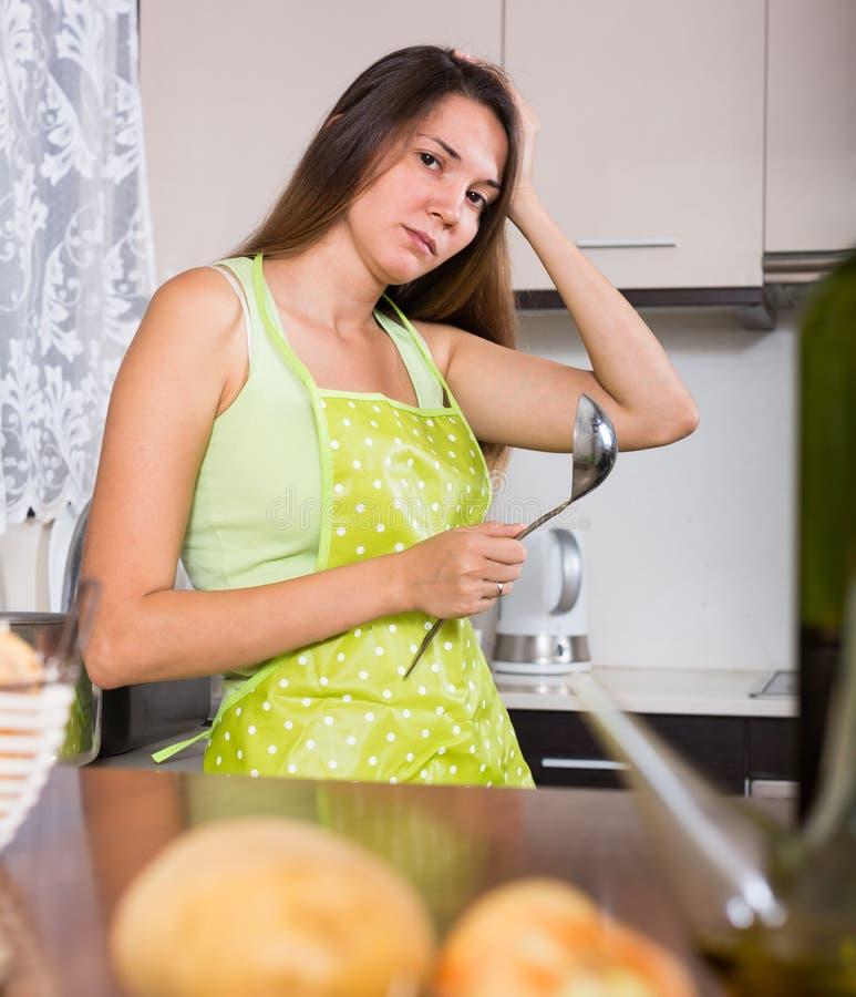 Huisvrouw die wat denken om voor diner voorbereidingen te treffen stock afbeeldingen