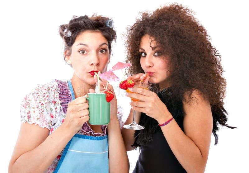 Huisvrouw en maniervrouw die een cocktail drinken stock foto's