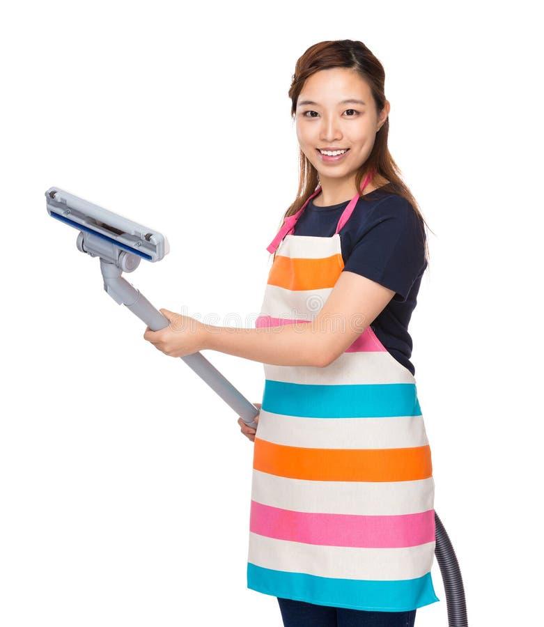 Huisvrouw het gebruiken van elektriciteits vacuümvlekkenmiddel stock afbeelding