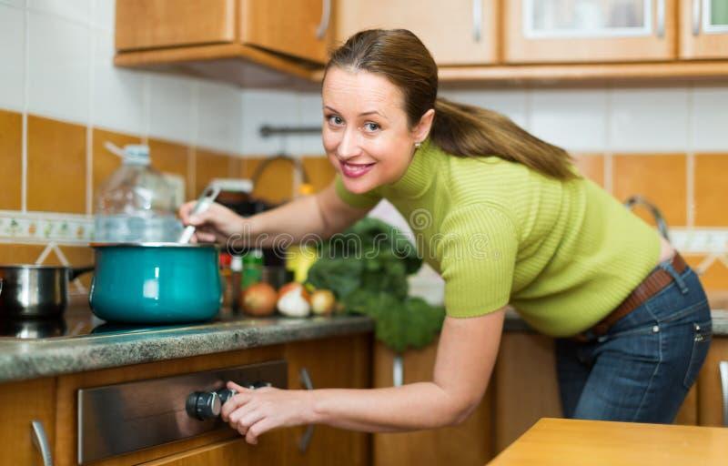 Huisvrouw het koken bij keuken royalty-vrije stock afbeelding