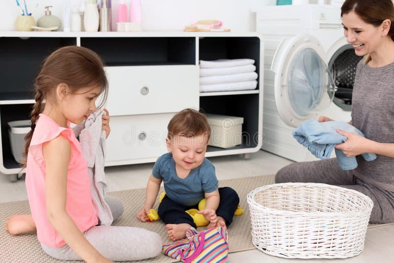 Huisvrouw met kinderen die vers gewassen kleren vouwen stock foto
