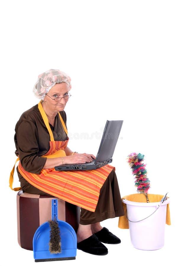 Huisvrouw op laptop stock foto