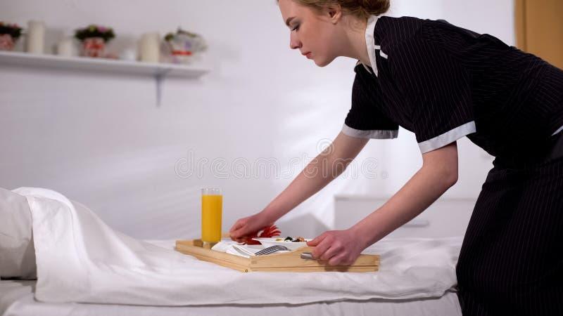 Huisvrouwen brengend ontbijt aan bed, voedselorde in hotelruimte, de kwaliteitsdienst royalty-vrije stock foto's