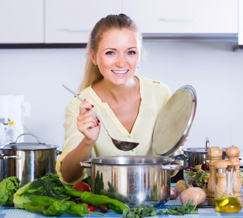 Huisvrouwen kokende groenten bij binnenlandse keuken stock fotografie