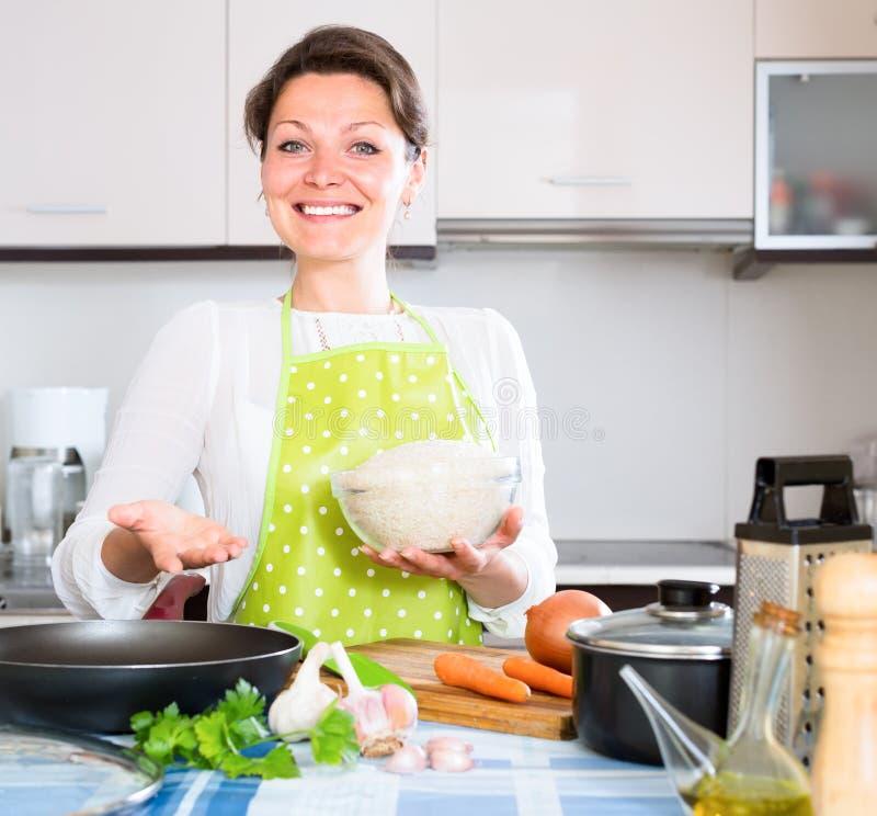 Huisvrouwen kokende paella in keuken stock afbeelding
