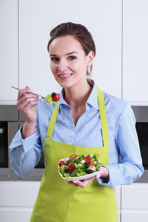 Huisvrouwen proevende salade in de keuken royalty-vrije stock afbeelding