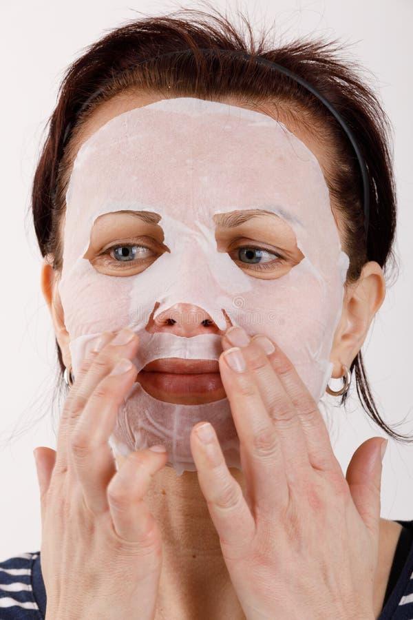 Huisvrouwenvrouw met een bladmasker op haar gezicht stock foto's