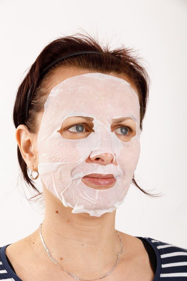 Huisvrouwenvrouw met een bladmasker op haar gezicht stock fotografie