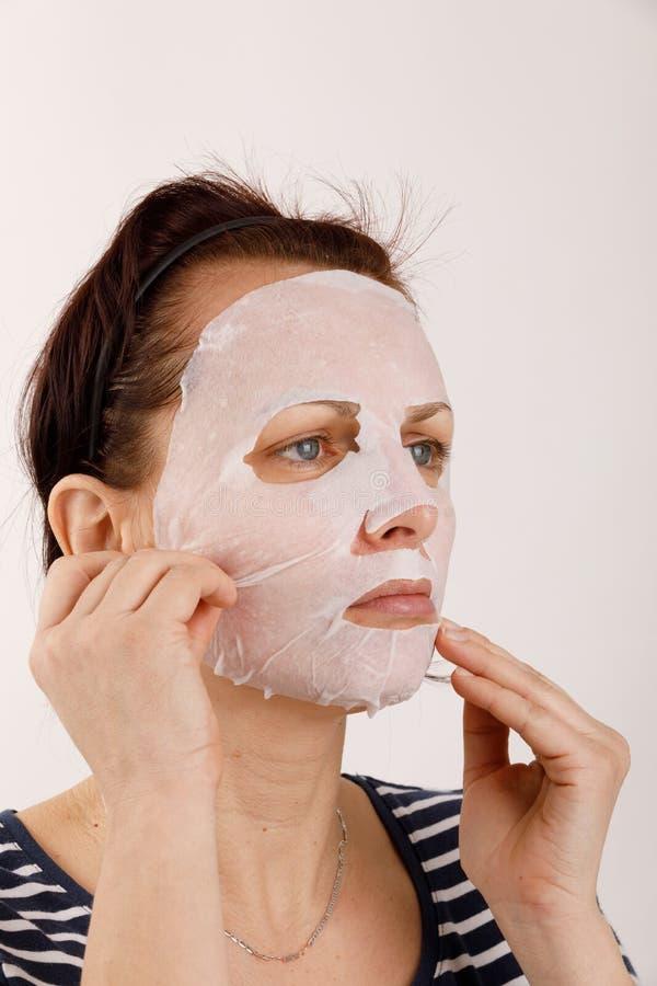Huisvrouwenvrouw met een bladmasker op haar gezicht stock foto