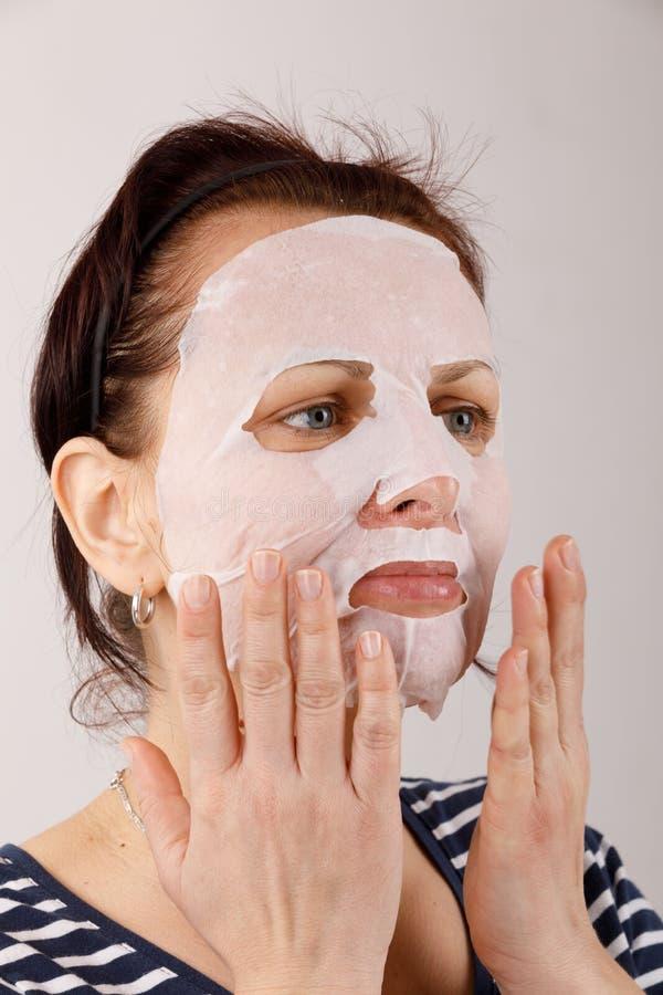 Huisvrouwenvrouw met een bladmasker op haar gezicht royalty-vrije stock foto's