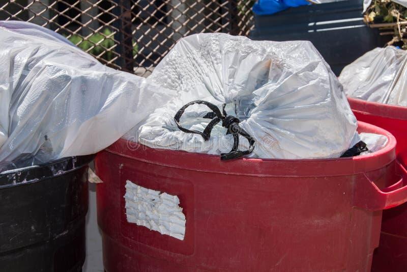 Huisvuil in zakken die in vuilnisbakken zitten royalty-vrije stock afbeelding