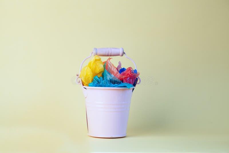 Huisvuilbak met kleurrijk plastiek voor recycling geïsoleerd op gele achtergrond royalty-vrije stock foto