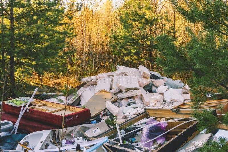Huisvuilstortplaats in de bos, slechte ecologie stock foto