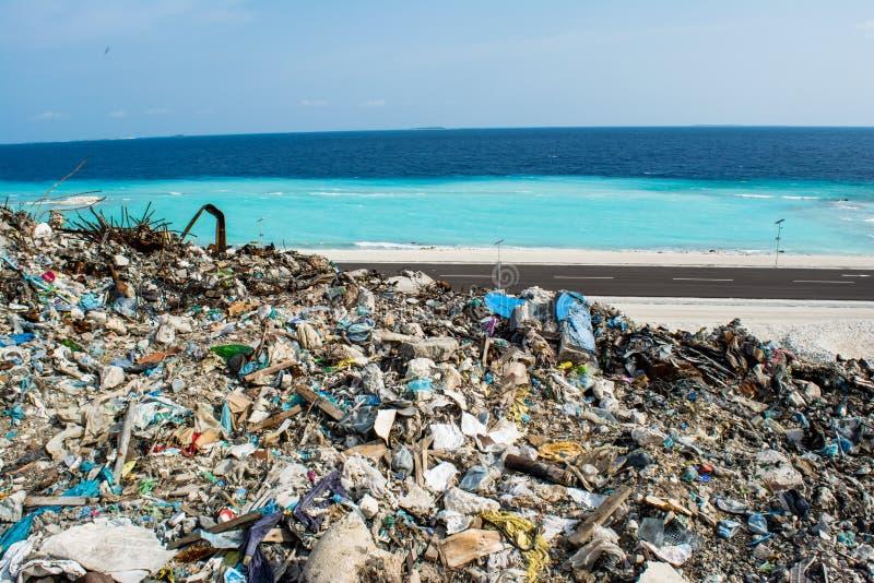 Huisvuilstortplaats dichtbij het strand dicht bij oceaanhoogtepunt van rook, draagstoel, plastic flessen, vuilnis en afval bij tr royalty-vrije stock afbeeldingen