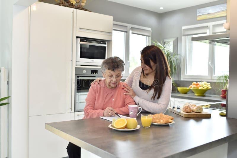Huiswerker uit de hulpverlening die een bejaarde bijstaan stock foto