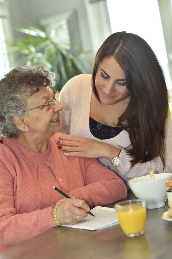 Huiswerker uit de hulpverlening die een bejaarde dame met kruiswoordraadsels helpen royalty-vrije stock foto