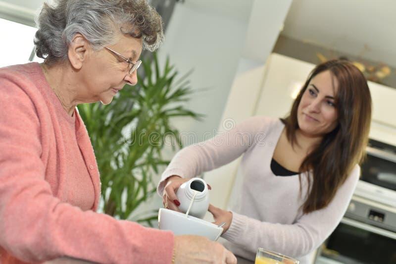 Huiswerker uit de hulpverlening die een thee dienen aan een hogere dame stock foto's