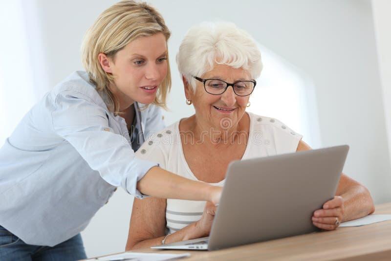 Huiswerker uit de hulpverlening en bejaarde die laptop met behulp van royalty-vrije stock fotografie