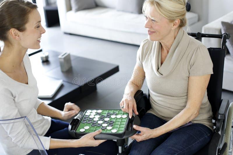 Huiswerker uit de hulpverlening met bejaarde die sociaal spel spelen royalty-vrije stock afbeelding
