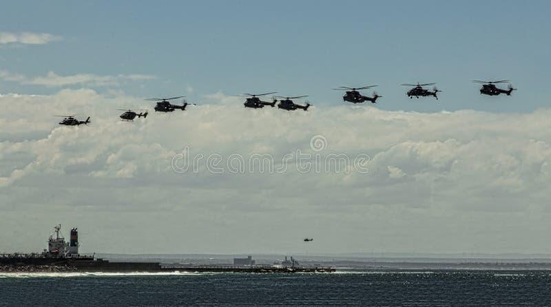 Huit hélicoptères dans la formation au-dessus d'un bateau photos libres de droits