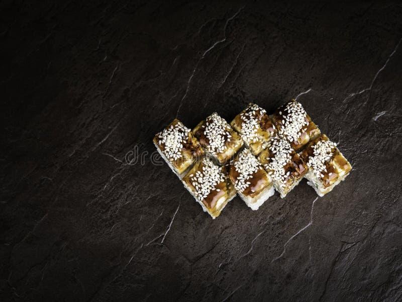Huit petits pains dans le style japonais sur une vue supérieure de fond foncé de soulagement photographie stock