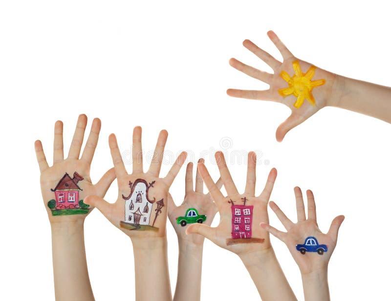 Huizen, auto en bomen op kinderenhanden die worden geschilderd Omhoog opgeheven handen royalty-vrije stock afbeeldingen