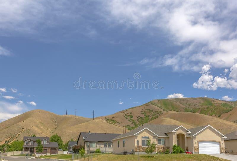 Huizen in de voorsteden met heuvels erachter en exemplaarruimte stock fotografie
