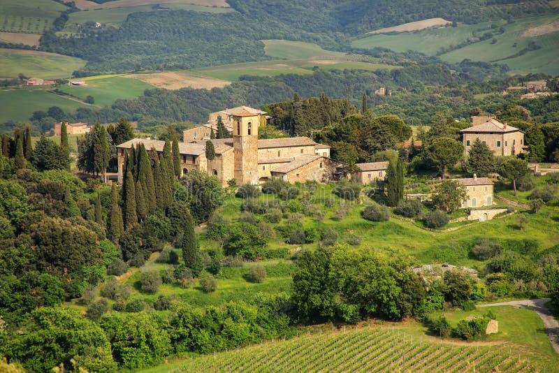 Huizen door bomen en gebieden in Val D ` Orcia, Toscanië, I worden omringd die royalty-vrije stock fotografie