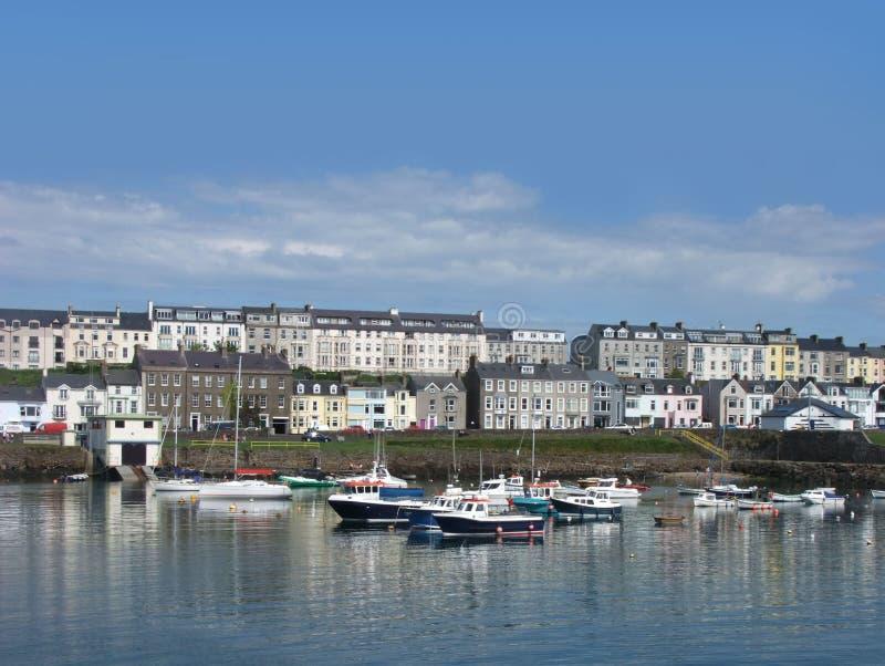 Huizen en boten in de haven door Iers overzees Co Antrim Noord-Ierland 2017 met blauwe hemelachtergrond voor het exemplaar van de royalty-vrije stock fotografie