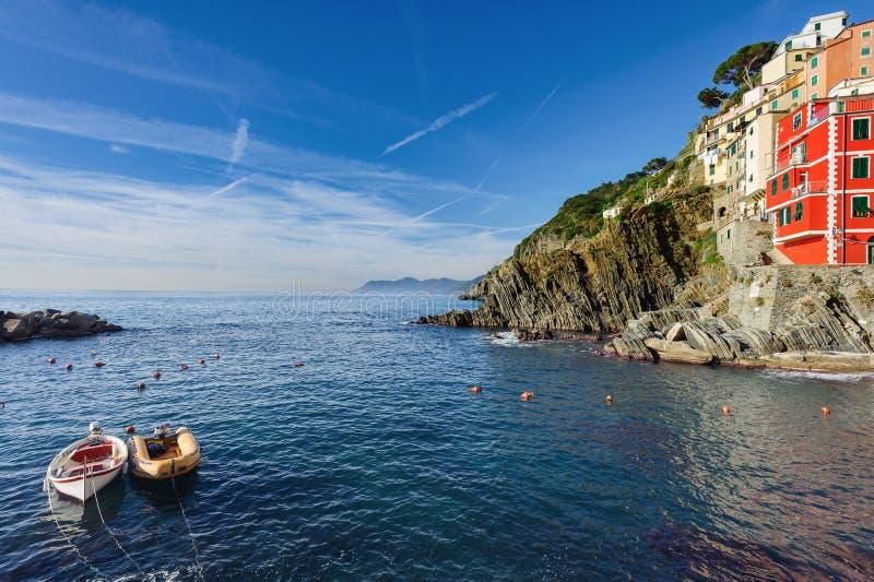 Huizen en overzeese baai met boten bij Riomaggiore-stad in het nationale park van Cinque Terre in Italië stock foto's