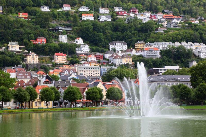 Huizen in kleine stad onder berg met fontein stock fotografie