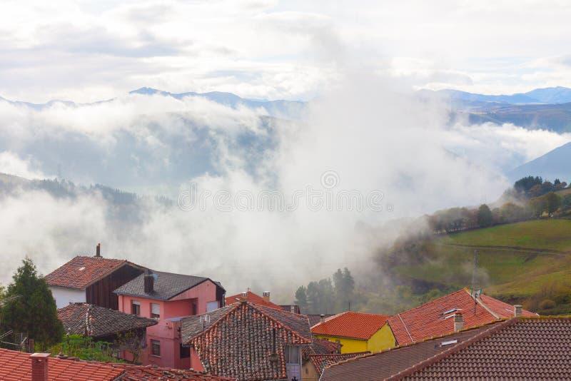 Huizen met bergen in de mist op de achtergrond in Tineo, Asturias, Spanje royalty-vrije stock foto's