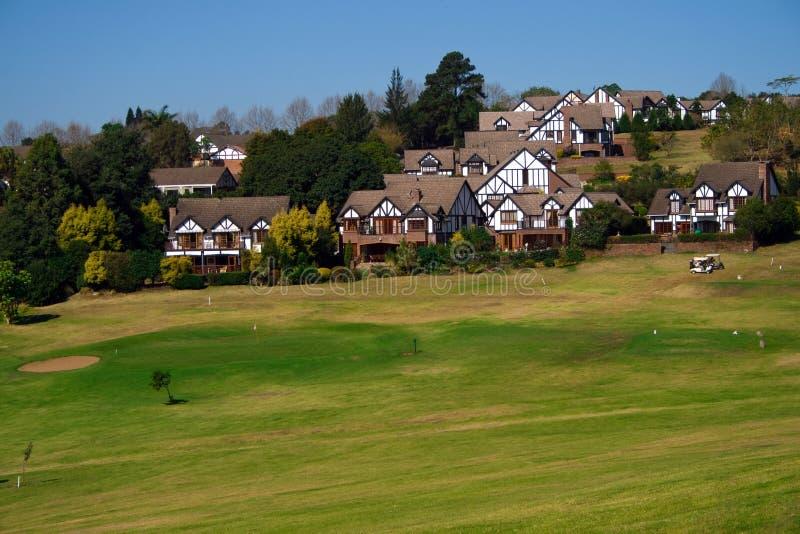 Huizen op golfcursus stock afbeelding