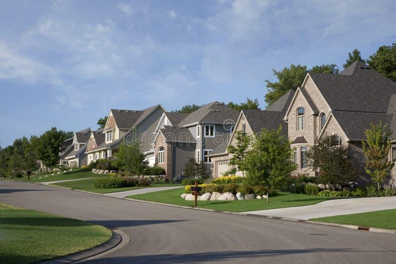 Huizen op straat in de voorsteden voor de betere inkomstklasse in ochtendzonlicht stock fotografie