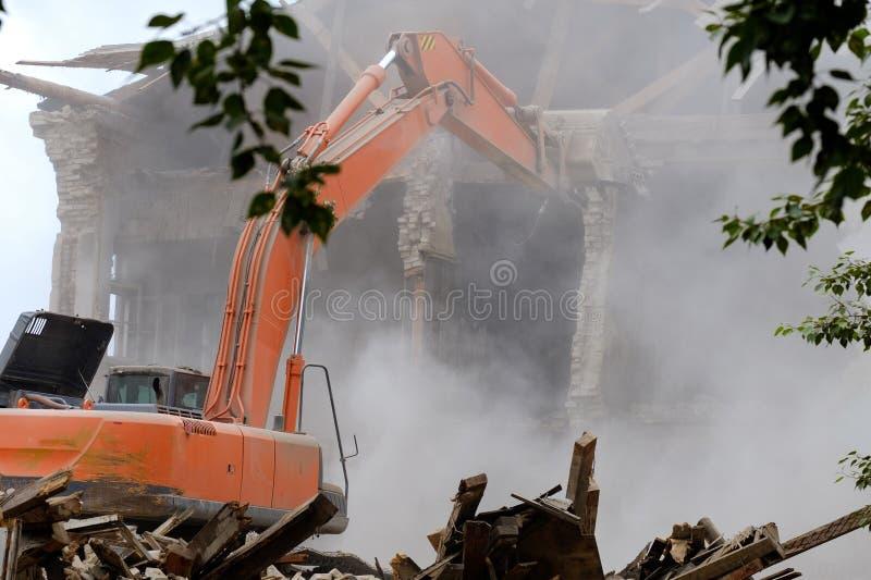 Huk ekskawator spisujący na budynku który rozmontowywał ściana spadał mnóstwo pył pod kołami trac fotografia royalty free