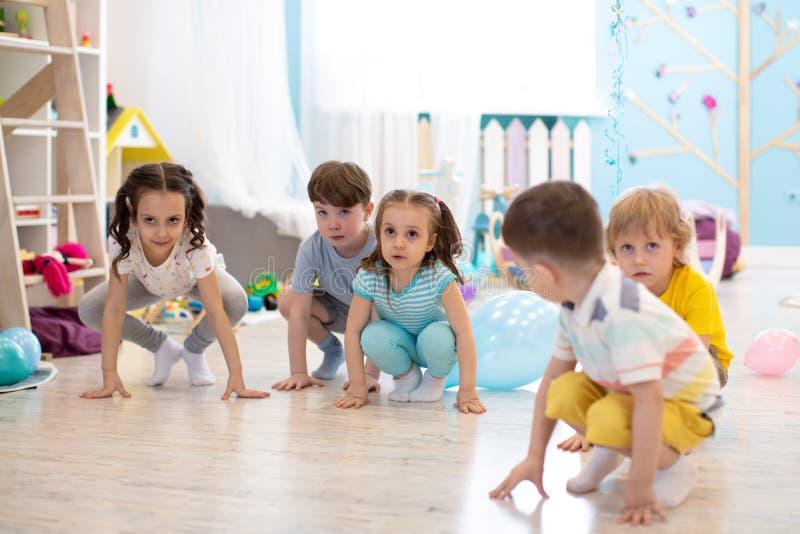 Huka sig ned barn som f?rbereds att hoppa Sportaktiviteter royaltyfri foto