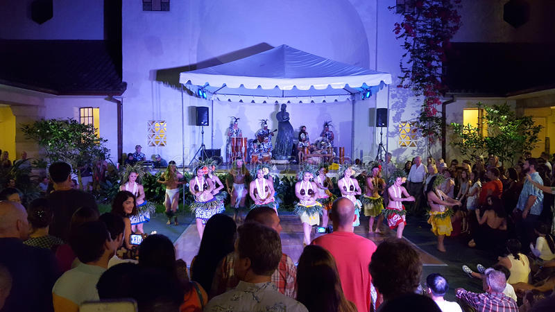 Hula dancers dance as musicians play on stage with crowd watching at Art After Dark event royalty free stock image