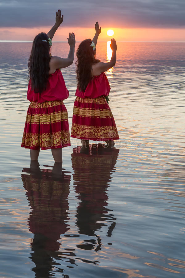 Hula dancers in ocean at sunset. Two young female hula dancers in the ocean with arms raised to the sun at sunset on Molokai, Hawaii stock photos