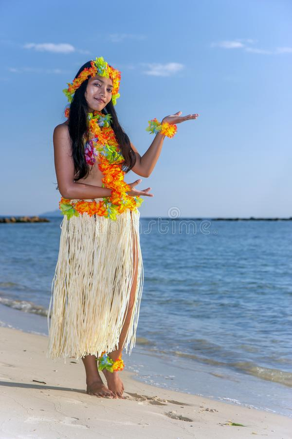 Hula Hawaii dancer dancing on the beach. With horizon of sea. Ethnic woman in costume dancer Hawaii hula dancing in a tropical island stock photo
