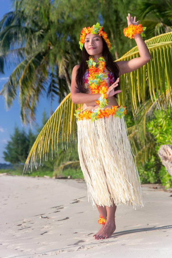Hula Hawaii dancer dancing on the beach. With palms trees. Ethnic woman in costume dancer Hawaii hula dancing in a tropical nature stock image