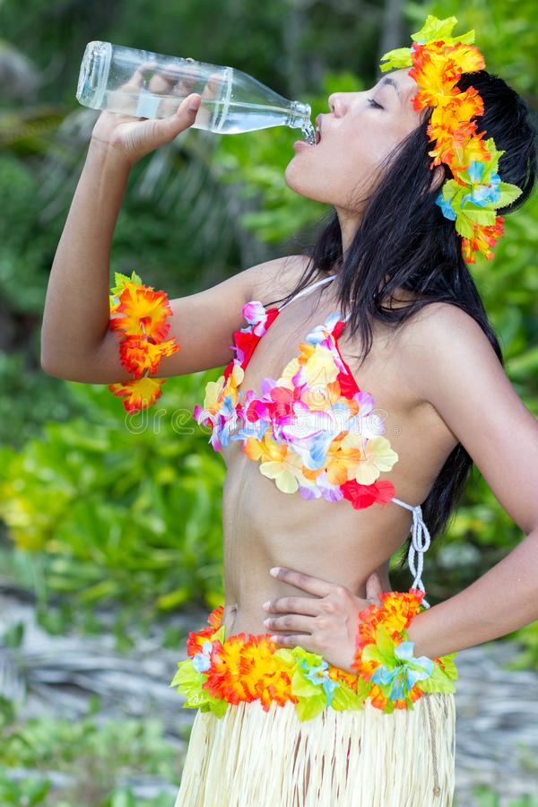 Hula Hawaii dancer drinks water from a bottle. Woman in costume Hula Hawaii dancer drinks water from a bottle stock images