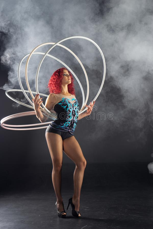 Beautiful female red hair circus artist holding hoops stock photos