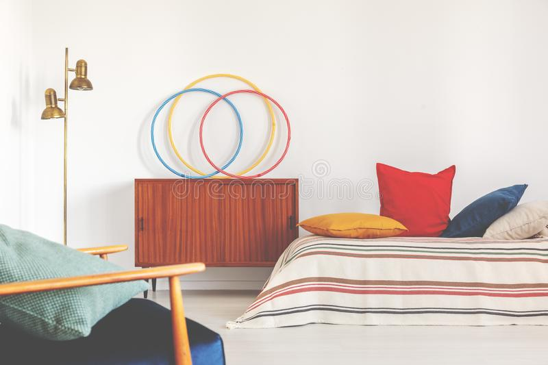 Hula hoops on a cupboard next to a bed with colorful pillows in a retro bedroom interior stock photos