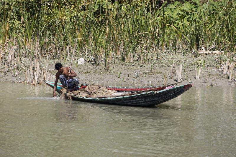 Hularhat, Bangladesh, 27 Februari 2017: De visser controleert zijn visnet een succesvolle vangst in zijn houten boot stock fotografie