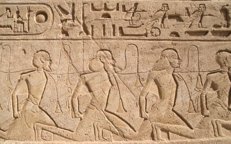 Hulp die een rij van gevangenen in Abu Simbel-tempel van Ramesses II, Egypte afschilderen stock foto