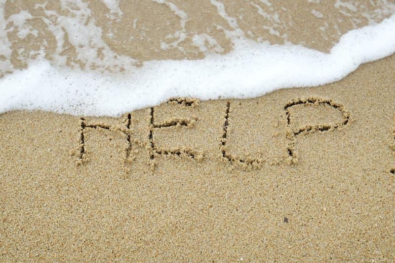Hulp die op zand wordt geschreven royalty-vrije stock fotografie