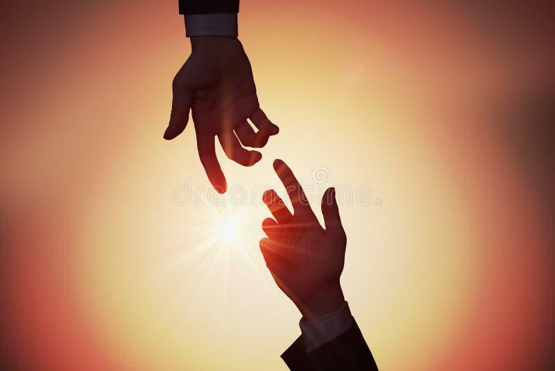 Hulp en hulpconcept Twee handen bereiken elkaar bij zonsondergang stock foto's