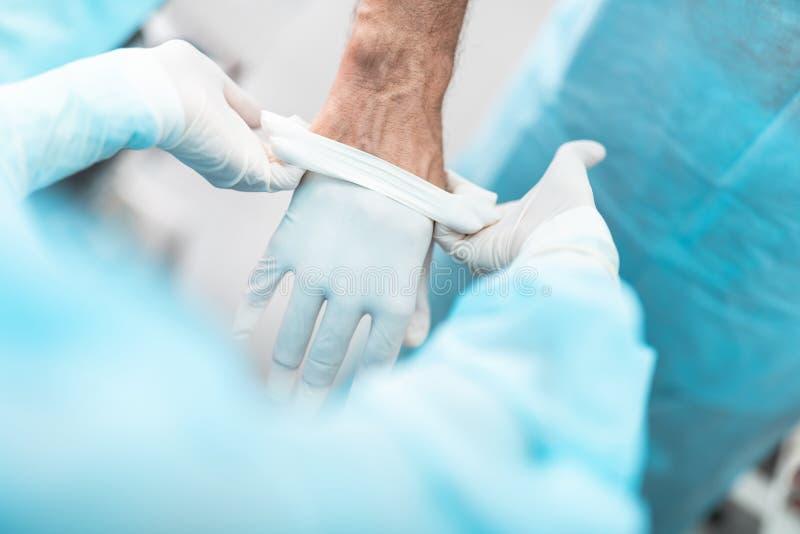 Hulp helpende arts om voor chirurgische operatie voorbereidingen te treffen stock afbeeldingen