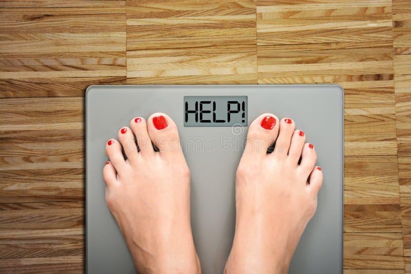 Hulp om kilogram te verliezen die met vrouwenvoeten op een gewichtsschaal stappen stock afbeeldingen