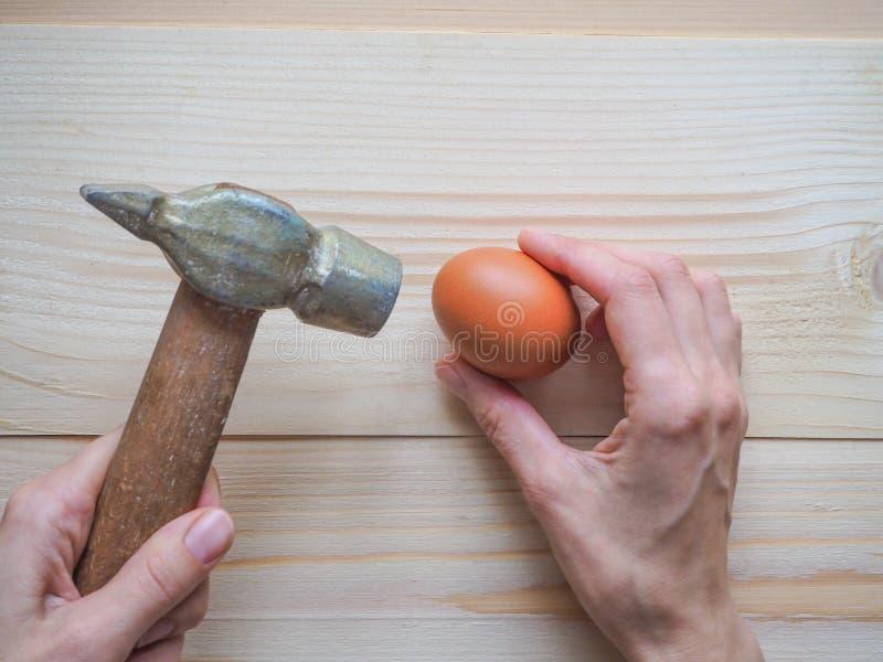 Hulpmiddel en ei op houten achtergrond Het concept complexe problemen, de uitdaging kan worden opgelost stock foto